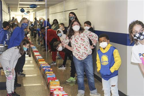 students and staff line the halls for cereal box dominos