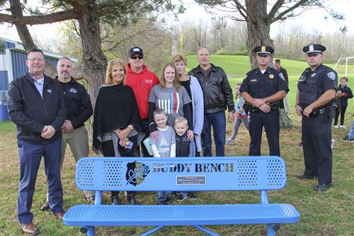 Crossley family and police officers stand behind buddy bench