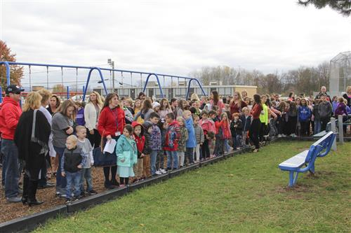 students and staff stand on the playground