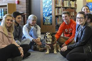 Group of students and owner sit with dog