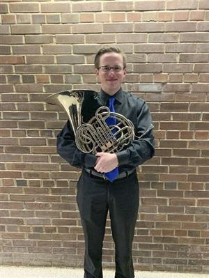 student poses with french horn