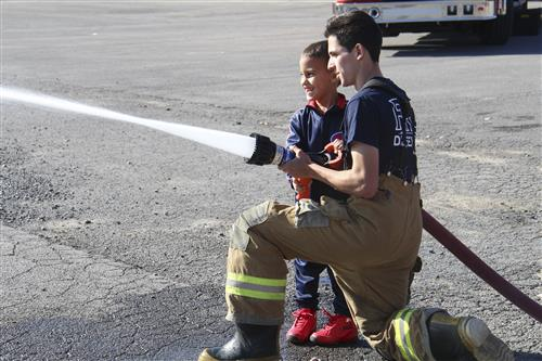 student and firefighter use fire hose